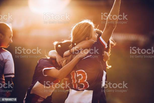 Team of happy female soccer players celebrating their achievement on a playing field at sunset.