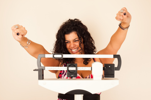 Woman celebrating weight loss on a medical weight scale.