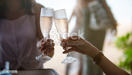 Close-up of women toasting with rose wine