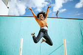 A beautiful African American woman smiles, jumping high in the air with her arms outstretched and a smile on her face.  Horizontal image with copy space.  Shot in Los Angeles, California.