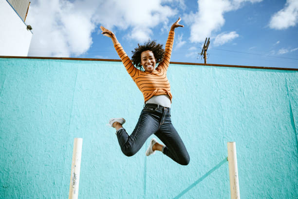 Celebrating Woman Jumps Into The Air A beautiful African American woman smiles, jumping high in the air with her arms outstretched and a smile on her face.  Horizontal image with copy space.  Shot in Los Angeles, California. mid air stock pictures, royalty-free photos & images