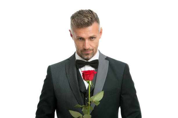 Celebrating womens day. Handsome man hold red rose. Flowers for womens day. Bachelor in formalwear. International womens day. March 8. Floral gift on womens day Celebrating womens day. Handsome man hold red rose. Flowers for womens day. Bachelor in formalwear. International womens day. March 8. Floral gift on womens day. bachelor stock pictures, royalty-free photos & images