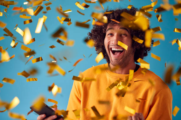 Celebrating Young Man With Mobile Phone Winning Prize And Showered With Gold Confetti In Studio stock photo