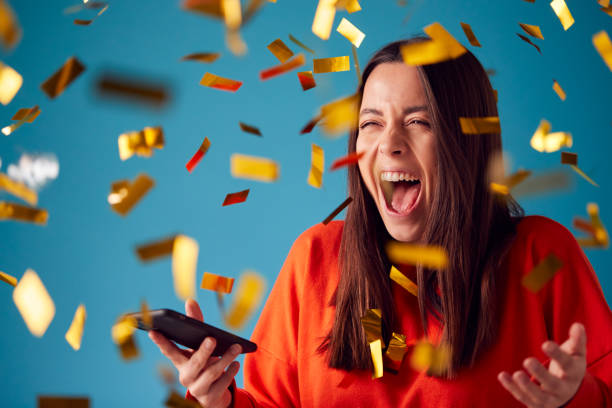 Celebrating Young Woman With Mobile Phone Winning Prize And Showered With Gold Confetti In Studio stock photo