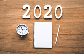 Celebration and countdown of new year 2020 concepts with text number and alarm clock and notepaper on wood background.top view