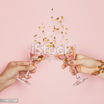 Two hands chin-chin. Wine glasses with gold confetti on pink background, celebration and holiday card composition