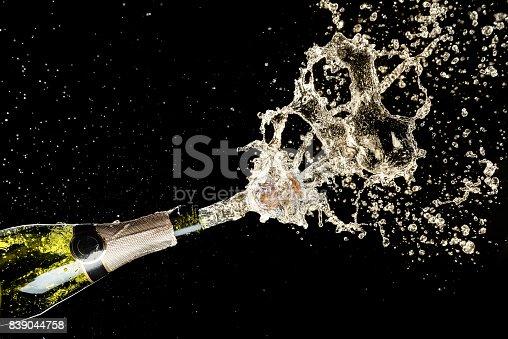 istock Celebration and holiday theme. Champagne splashes on black background 839044758