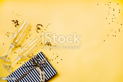 istock Celebration background - top view of two chrystal champagne glasses, a gift box wrapped in black and white striped paper, ribbons and star shaped golden confetti over yellow background. Copy space. 939402160