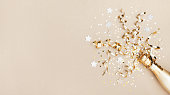 Celebration background with golden champagne bottle, confetti stars and party streamers. Christmas, birthday or wedding concept. Flat lay style.