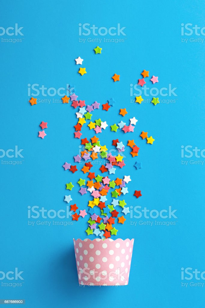 Celebration concept. Cupcake paper cup with colorful stars on a blue background. Top view stock photo