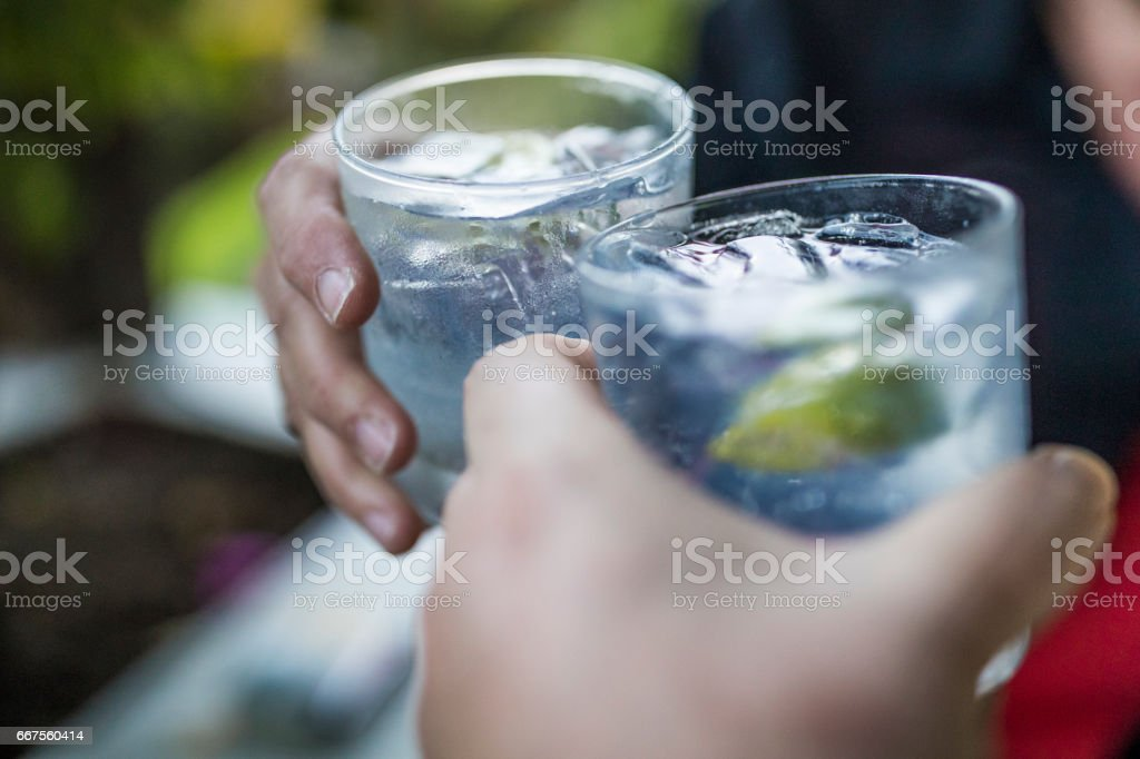 Celebration concept with hand close-up of a couple celebrating the beginning of their vacations with each a gin & tonic. stock photo