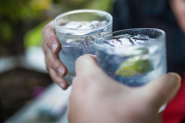 Concept de célébration avec main gros plan d'un couple célébrant le début de leurs vacances avec chacun un gin & tonique. - Photo