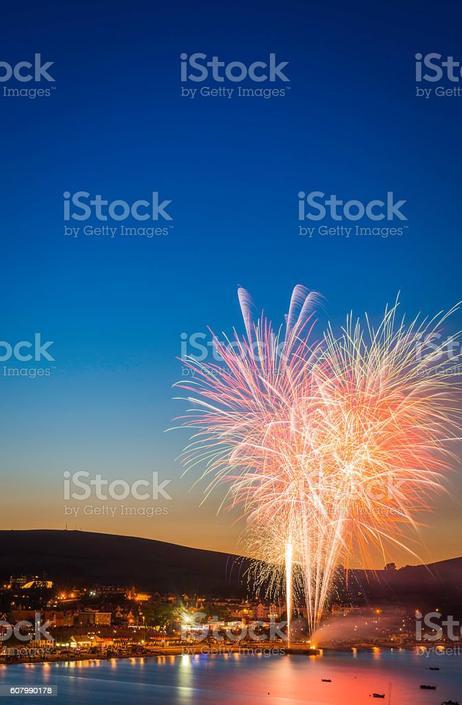 Celebration fireworks exploding in blue sunset sky over seaside town stock photo