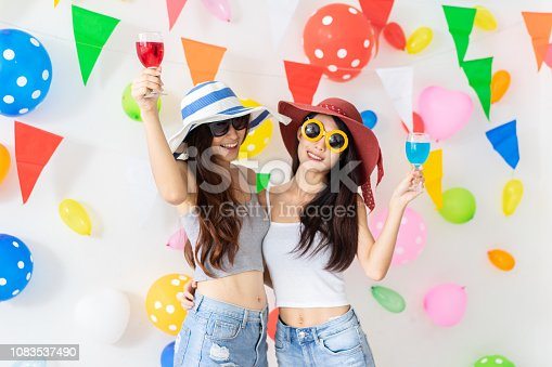 istock celebration new year or birthday party group of asian young woman and confetti happy,funny concept.drinking wine happy and fun in new year celebrate, color balloon  background. 1083537490