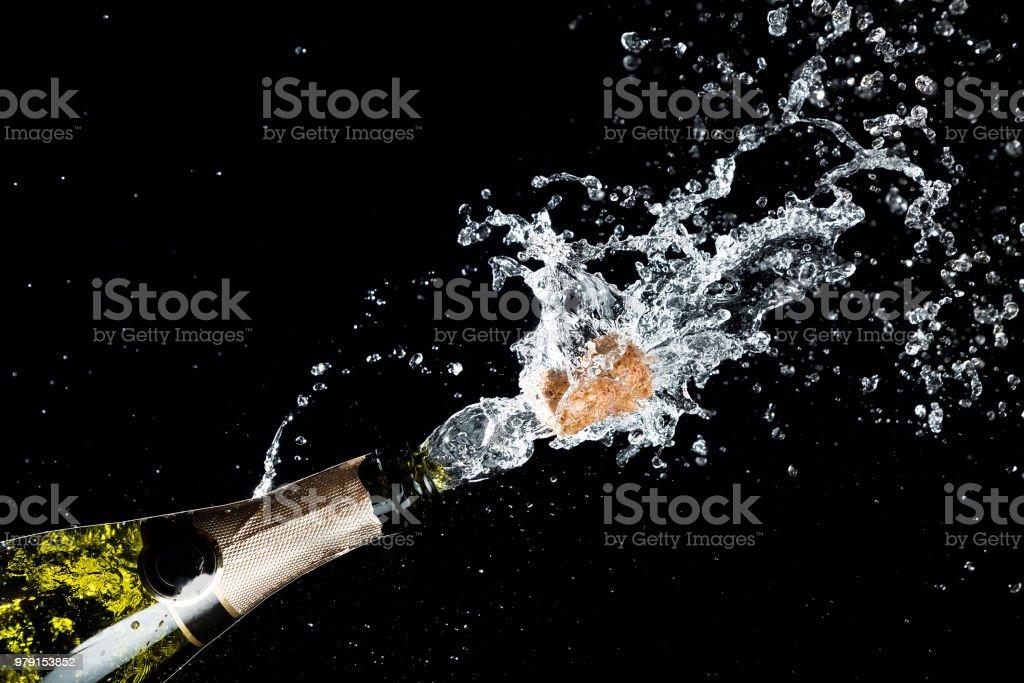Célébration de l'anniversaire ou thème de Noël. Explosion d'éclaboussure champagne mousseux avec des volants de Liège de la bouteille sur fond noir. - Photo