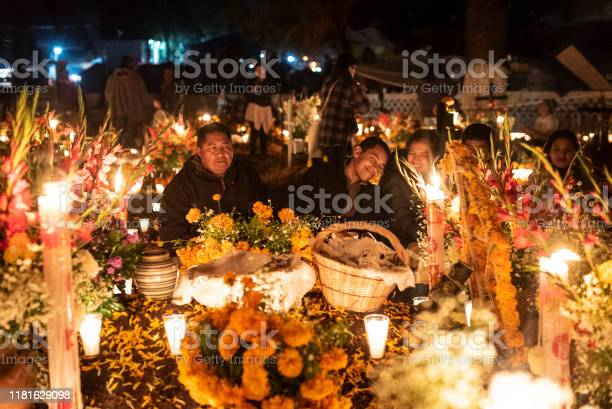 Celebration of Mexican Day of the Dead at Tzintzuntzan Cemetery in the Pátzcuaro Region of Michoacán State. Tzintzuntzan, 02/11/2018: Family gathered in front of a tomb in the cemetery located in Tzintzuntzan in the region of Patzcuaro, in the Mexican state of Michoacan. On November 1st and 2nd, the local community gathers in the cemetery to celebrate Day of the Dead, when, according to Mexican belief, the souls of the dead return to visit their families. During the celebration the tombs are adorned with flowers, candles and the favorite foods of the deceased as a way to welcome their souls in a joyful way. Candle Stock Photo