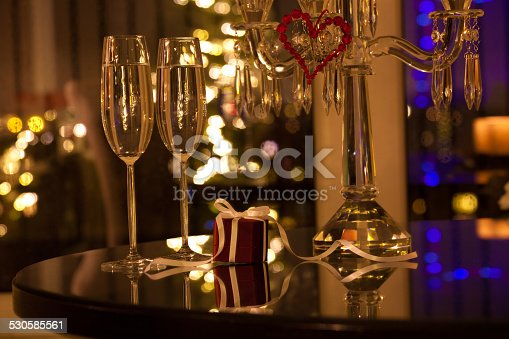 Elegant glasses of champagne with beautiful gift box. Luxury present on festive lighted background.