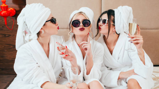celebration spa congratulation women champagne Celebration party at spa. Friends congratulation. Young women with champagne. Sunglasses, bathrobes and turbans on. spa stock pictures, royalty-free photos & images