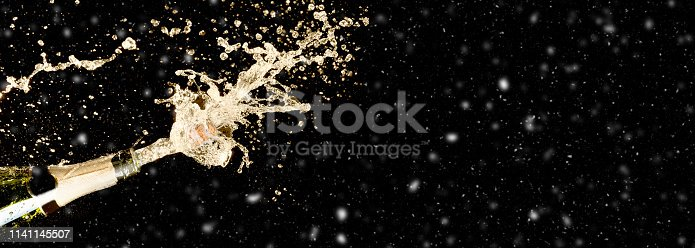 istock Celebration theme with splashing champagne on black background with snow and free space. Christmas or New Year, Valentines day background. 1141145507