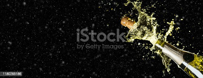istock Celebration theme with splashing champagne on black background with snow and free space. Christmas or New Year, Valentines day background. Wide banner format party mockup. 1180265186