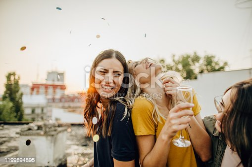Photo of girlfriends on the rooftop, celebrating their friendship