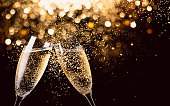 Two glasses of champagne toasting in the nigh with lights bokeh, glitter and sparks on the background