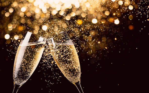 Celebration toast with champagne Two glasses of champagne toasting in the nigh with lights bokeh, glitter and sparks on the background celebration stock pictures, royalty-free photos & images