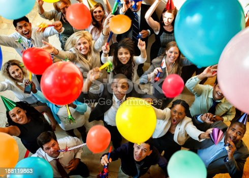 Business people having a party with balloons, hats and horns.