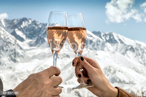 Couple in celebration with rosé champagne at foot of the snowy Alps.