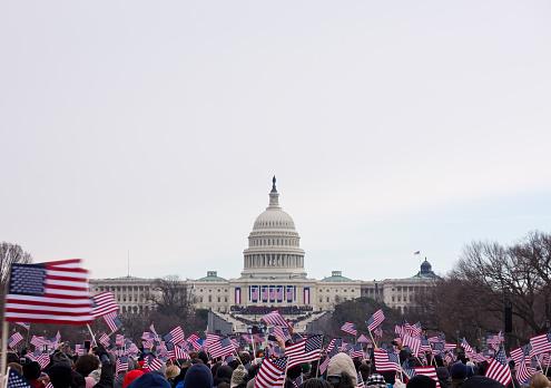 2013 Presidential Inauguration of Barack Obama.  Flag waving spectators throng the Washington Mall near the capital.