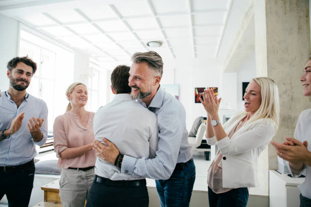 Celebrations In Office After Successful Business Pitch By Team An office team are celebrating together, embracing and applauding each other after a successful business pitch. passion stock pictures, royalty-free photos & images