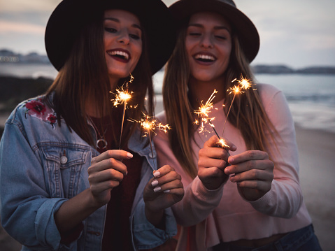 Two beautiful friends celebrating holding sparklers at beach