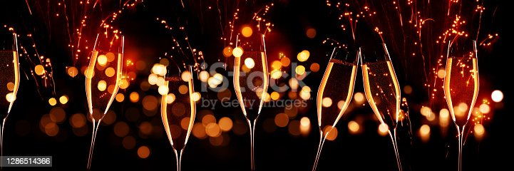 Celebrations with champagne in front of red glittering fireworks sky and golden bokeh. Horizontal background for silvester and wedding. Special occasion concept.