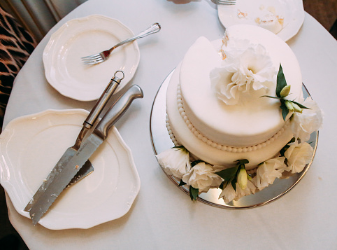 celebratory cake white on a table with cutlery