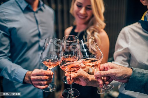 Happy people drinking rose wine together