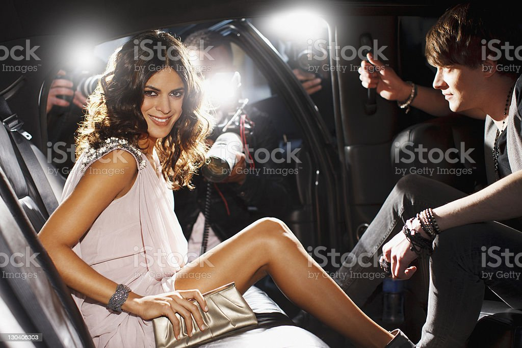 Celebrities emerging from car towards paparazzi stock photo