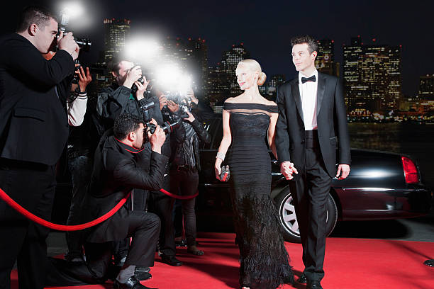 celebrities posing for paparazzi on red carpet - fame stock photos and pictures