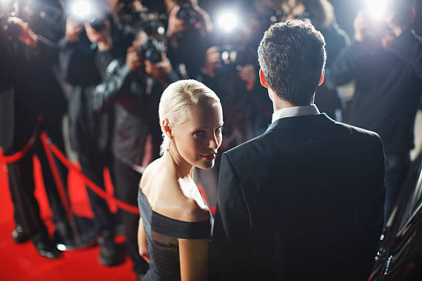 celebrità in posa per paparazzi sul red carpet - fama foto e immagini stock