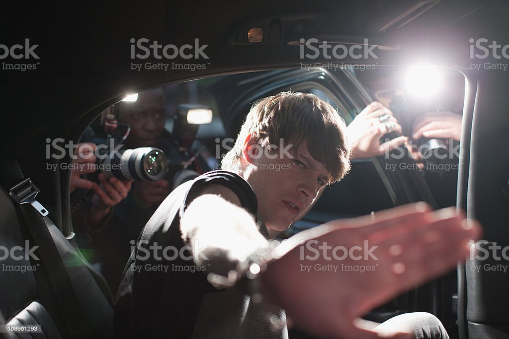 Celebrity blocking photo in backseat of limo royalty-free stock photo