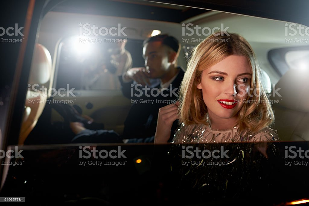 Celebrity couple in back of a car, photographed by paparazzi stock photo