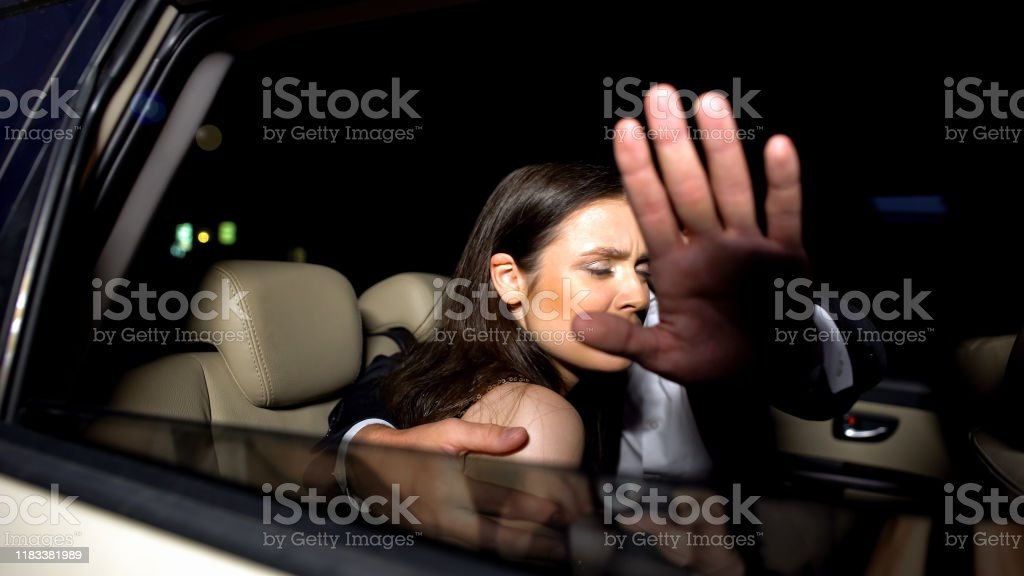 Celebrity couple in car hiding with hand from magazine photographers...