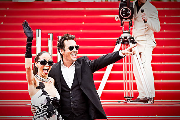 celebrity couple on red carpet in cannes - film festival stock photos and pictures