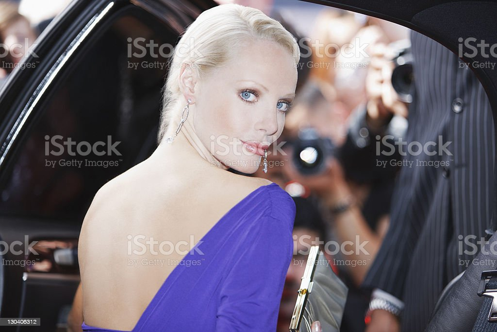 Celebrity emerging from car towards paparazzi stock photo