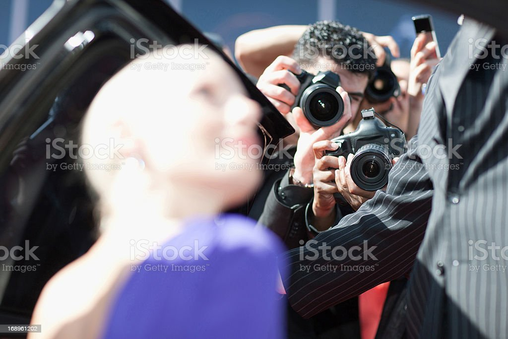 Celebrity emerging from car towards paparazzi royalty-free stock photo
