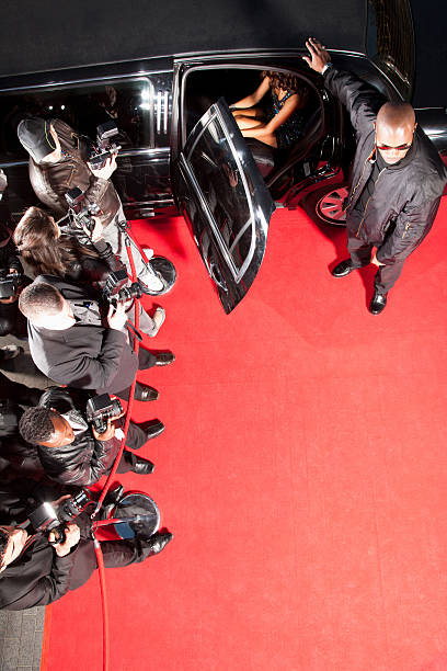 Celebrity getting out of limo on red carpet stock photo