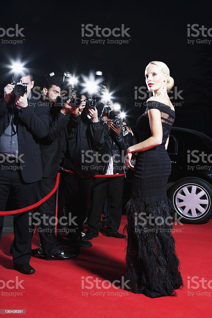 Celebrity posing for paparazzi on red carpet stock photo