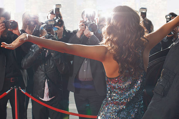 celebrity posing for paparazzi on red carpet - fame stock photos and pictures