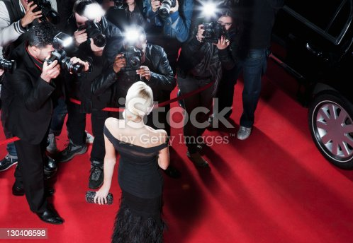 istock Celebrity posing for paparazzi on red carpet 130406598