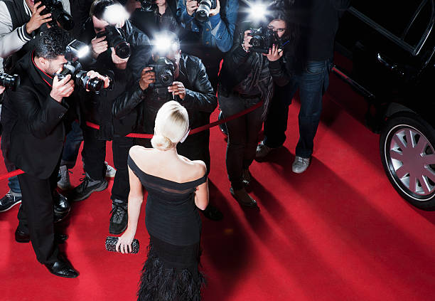 celebrity posing for paparazzi on red carpet - arts culture and entertainment stock pictures, royalty-free photos & images