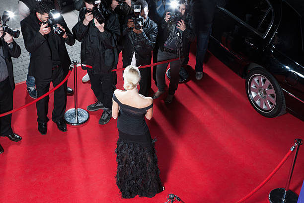 Celebrity posing for paparazzi on red carpet  Fame stock pictures, royalty-free photos & images